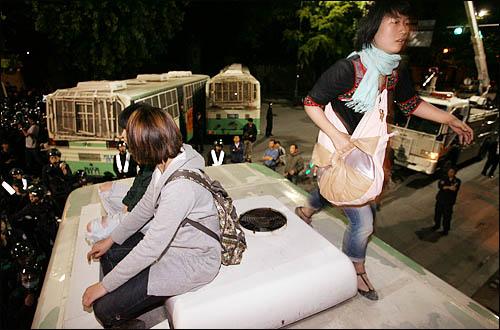 """31일 밤 서울 삼청동에서 청와대 방향으로 진격하는 시위대를 막기 위해 경찰이 전경차를 동원해 길을 막자 일부 학생들이 전경차에 올라가 """"이명박 나와라""""를 외치고 있다."""