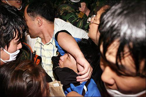 1일 새벽 서울 삼청동에서 청와대 방향으로 돌진하던 시위대가 이들을 가로막는 경찰과 몸싸움이 벌어져 부상자가 속출하고 있다. 부상당한 한 시민이 응급차로 옮겨지고 있다.