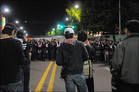 대치 11시 34분. 광화문 서편 도로. 청와대로 향하는 길목에서 시민들이 경찰병력과 대치 중이다. 그러나 이때까지만 해도 시민들이 경찰병력을 배경으로 기념사진을 찍는 등 여유로운 상황이었다. 그러나 불과 15분여 후 경찰의 물대포 세례가 시작되면서 상황은 급속도로 악화되기 시작했다.