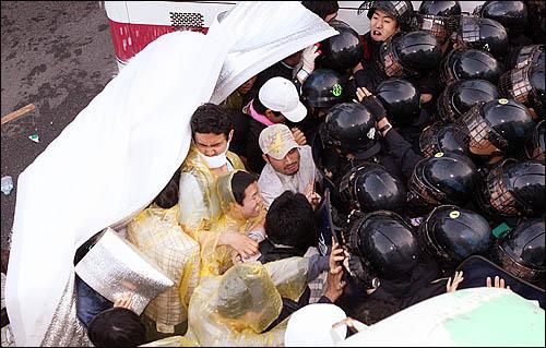 서울 삼청동에서 청와대 방향으로 진입하려는 집회 참가자들에게 1일 아침 경찰이 물대포를 쏘며 진압을 시도하자 시위대가 필사적으로 밀어내고 있다.