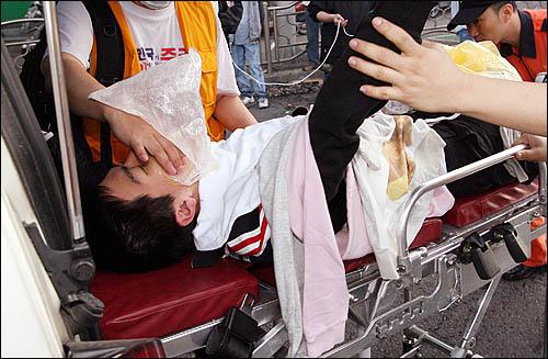 미국산 쇠고기 수입에 반대하며 서울 삼청동에서 청와대 방향으로 진입하려던 집회 참가자가 1일 아침 경찰 진압과정에서 다쳐 응급차에 실려가고 있다.