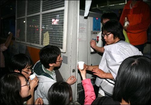 경찰버스에서 물마시기 1일 저녁 광화문 네거리에 모인 촛불문화제 참가자들이 끌어낸 버스 안에 있는 급수기에서 물을 뽑아 마시고 있다.
