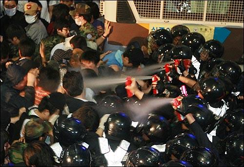 1일 밤 서울 세종로 사거리에서 미국산 쇠고기 수입반대를 요구하며 시위를 벌이던 학생, 시민들에게 경찰들이 휴대용 소화기를 분사하고 있다.