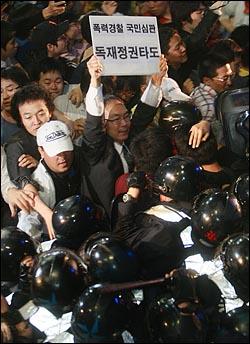 광우병위험 미국산쇠고기 수입반대 및 재협상을 요구하는 한 시민이 1일 밤 서울 세종로 사거리에서 경찰들과 대치를 벌이며  '폭력경찰 국민심판','독재정권 타도' 손피켓을 들어보이고 있다.