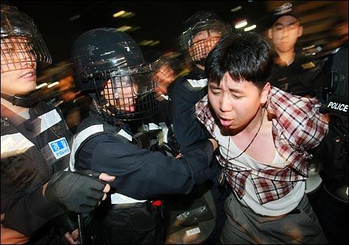 광우병위험 미국산쇠고기 수입반대 및 재협상을 요구하는 시민이 2일 새벽 서울 세종로 사거리에서 재협상을 요구하며 시위를 벌이다가 경찰에게 연행되고 있다.