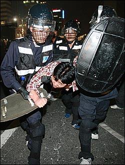 광우병위험 미국산쇠고기 수입반대 및 재협상을 요구하던 한 시민이 2일 새벽 서울 세종로 사거리에서 재협상을 요구하며 시위를 벌이다가 경찰에게 연행되고 있다.