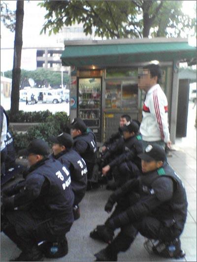 사복 경찰로 추정되는 청년 2명이 전의경들 사이에 서 있다.