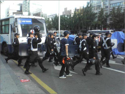 파란 티셔츠와 모자, 운동화를 착용하고 가방을 든 채 경찰대열에 맞춰 도로를 건너가는 한 청년이 보인다. 도로를 건너기 전 인도에서 경찰대열 사이에 앉아있는 것을 목격하였다.