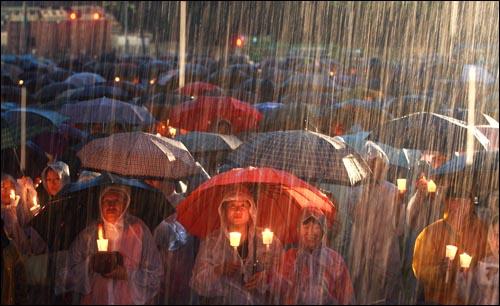 꽃다발 대신 촛불이다. 쏫아지는 빗속에서도 꽃다발 대신 촛불을 든 애국적 시민들의 결연함을 보라.