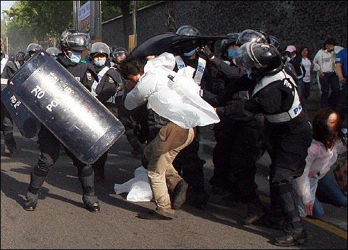 1일 오전 7시 45분경 서울 안국동 네거리에서 강제해산작전에 나선 경찰들이 한 시민을 에워싼 가운데 2명이 방패로 머리와 하체를 공격하고, 다른 1명은 몽둥이로 등을 때리고 있다.