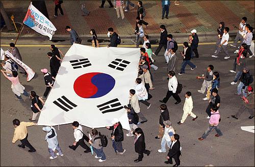 5일 밤 서울 세종로 사거리에서 미국산 쇠고기 수입에 반대하며 밤샘 농성을 벌이던 일부 시민들이 서대문 경찰청으로 이동, 폭력진압에 항의한 뒤 태극기를 앞세워 거리행진을 하고 있다.