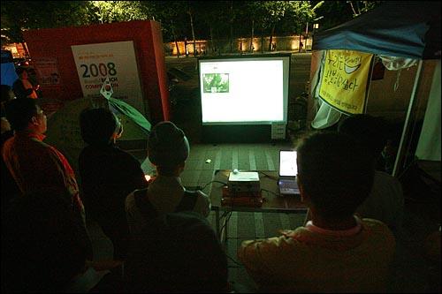 광우병국민대책회의가 '72시간 릴레이 농성'에 돌입한 가운데 6일 새벽 서울시청앞 광장에서 참여연대가 스크린에 오마이뉴스 생중계를 상영하자, 시민들이 모여 72시간 릴레이 집회 생중계를 지켜보고 있다.
