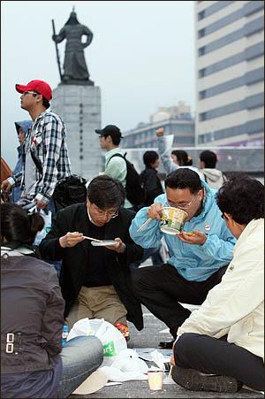미국산 쇠고기 수입에 반대하며 서울 세종로 사거리에서 밤새 농성을 벌인 시민들이 6일 아침 컵라면으로 허기를 달래고 있다.