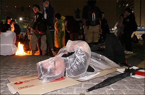 미국산 쇠고기 수입에 반대하며 서울 세종로 사거리에서 밤새 농성을 벌인 시민들이 바닥에 종이 박스를 깔고 6일 새벽 새날을 맞이하고 있다.