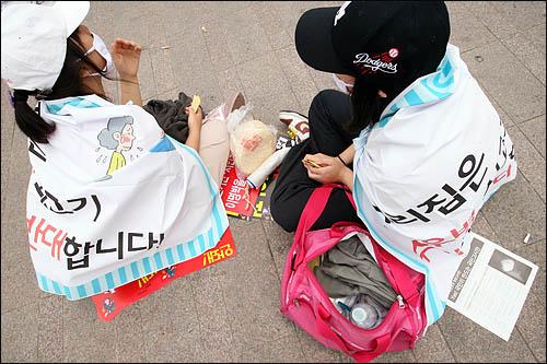 전북 전주에서 상경한 여고생들이 6일 아침 '우리집은 광우병 쇠고기 수입에 반대합니다' 펼침막을 몸에 두르고 서울시청 앞 광장에 앉아있다. 급히 꾸려온 가방엔 밤샘 농성에 대비한 옷가지와 물, 뻥튀기 등이 들어 있다.