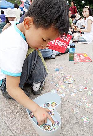 6일 아침 아빠 손을 붙잡고 경기도 오산에서 올라온 7살 소년. 72시간 릴레이 농성이 열리고 있는 서울광장엔 또래 아이들도 많지만 아직은 쑥스러워 딱지치기에 푹 빠져있다.