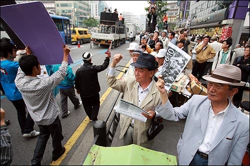 미국산 쇠고기 전명수입개방 반대 72시간 릴레이 농성 둘째날인 6일 오후 서울 대학로에서 집회를 마친 시민, 학생들이 촛불문화제가 열리는 서울시청앞 광장을 향해 행진을 벌이자 종로3가에서 거리에 나와 있던 노인들이 박수를 치고 함께 팔을 흔들며 격려하고 있다.
