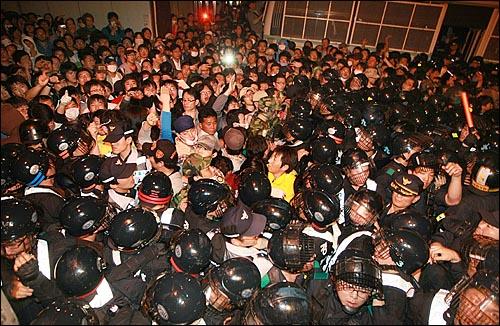 미국산쇠고기 전면 수입개방 반대 72시간 릴레이 촛불문화제 삼일째인 7일 새벽 서울 시청 앞 광장에서 열린 촛불문화제를 마친 학생과 시민들이 새문안교회 뒤쪽에서 경찰들과 대치하며 몸싸움을 하고 있다.