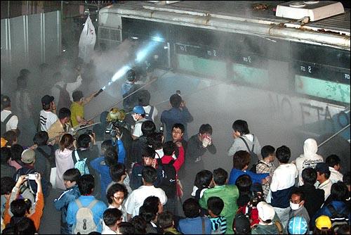 미국산쇠고기 수입 전면개방 반대 72시간 릴레이 농성 세번째날인 7일 새벽 서울 신문로 한글회관앞에서 경찰버스를 끌어내려는 시민, 학생들에게 소화기를 뿌리고 있다.