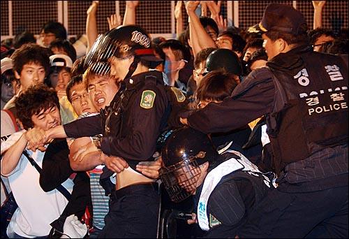 미국산쇠고기 전면 수입개방 반대 72시간 릴레이 촛불문화제 삼일째인 7일 새벽 서울 시청 앞 광장에서 열린 촛불문화제를 마친 학생과 시민들이 새문안교회 뒤쪽에서  대치를 벌이다가 전경대원을 한명씩 끌어내고 있다.