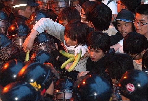 미국산쇠고기 수입 전면개방 반대 72시간 릴레이 농성 세째날인 7일 새벽 세종로네거리에서 청와대로 향하는 골목길에서 경찰과 대치하던 시위자들이 오이를 경찰에게 건네고 있다.