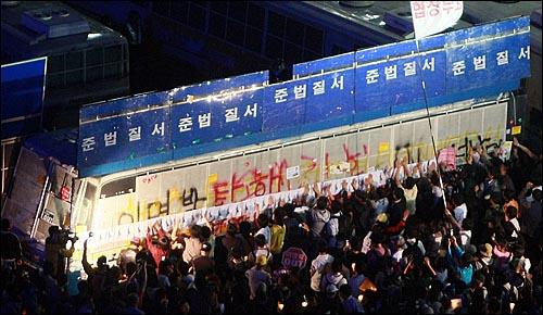 미국산쇠고기 전면 수입개방 반대 72시간 릴레이 촛불문화제 사흘째인 7일 밤 서울 시청 앞 광장에서 열린 촛불문화제를 마치고 세종로 사거리에 모인 학생과 시민들이 전경버스에 거리행진이 막히자 손으로 전경버스를 두드리며 미국산 쇠고기 전면 재협상을 요구하고 있다.