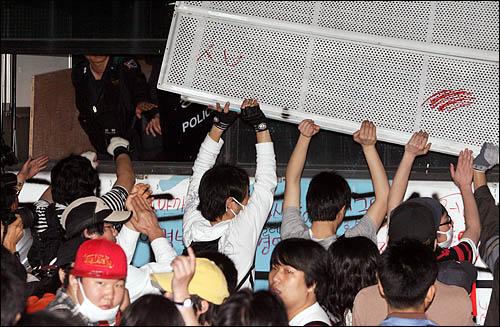 7일 밤 서울 안국동에서 청와대로 향하던 촛불행렬이 전경차에 가로막히자 진입하기 위해 차량 구조물을 뜯어내고 있다.