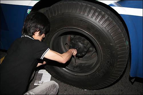 7일 밤 서울 안국동에서 청와대로 향하던 촛불행렬이 전경차에 가로막히자 전경차 타이어의 공기를 빼고 있다.