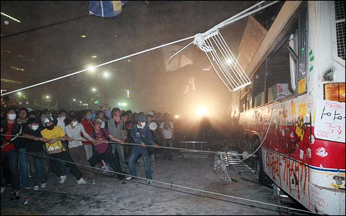 미국산쇠고기 전면 수입개방 반대 72시간 릴레이 촛불문화제 나흘째인 8일 새벽 서울 세종로 사거리에서 학생과 시민들이 청와대로 진출을 시도하기 위해 전경버스를 밧줄로 묶어 끌어내고 있다.