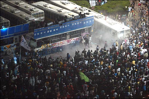 미국산쇠고기 수입 전면개방 반대 72시간 릴레이 농성 나흘째인 8일 새벽 서울 세종로 네거리에서 청와대 진출을 시도하는 시민, 학생들이 버스로 바리케이트를 친 경찰과 격렬하게 충돌하고 있다.