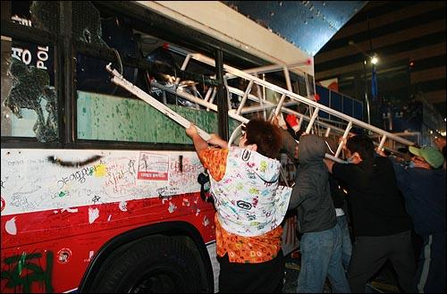 미국산쇠고기 전면 수입개방 반대 72시간 릴레이 촛불문화제 나흘째인 8일 새벽 서울 세종로 사거리에서 학생과 시민들이 청와대로 진출을 시도하기 위해 전경버스 창문을 사다리를 이용해 파손시키고 있다.