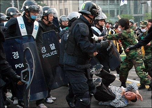 미국산쇠고기 전면 수입개방 반대 72시간 릴레이 촛불문화제 나흘째인 8일 오전 서울 세종로 사거리에서 밤샘 시위를 벌이던 학생과 시민들을 경찰이 강제해산을 시키는 가운데 한 시민이 경찰들에게 밀려 넘어지고 있다.