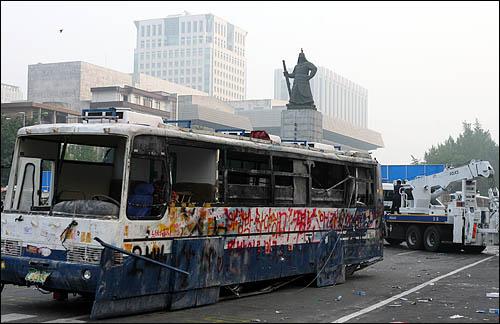 청와대 진입로인 서울 세종로 사거리에서 시위대가 끌어낸 전경차를 8일 새벽 경찰이 견인조치하고 있다. 차량 뒤로 외교통상부와 정부종합청사 건물이 보인다.
