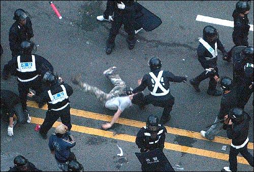 미국산쇠고기 수입 전면개방 반대 72시간 릴레이 농성 나흘째인 8일 새벽 서울 세종로네거리에서 밤을 새워 격렬한 시위가 벌어진 가운데 진압에 나선 경찰이 한 시민의 목을 낚아채서 땅바닥에 쓰러뜨리고 있다.