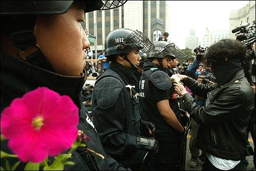 미국산쇠고기 수입 전면개방 반대 72시간 릴레이 농성 나흘째인 8일 새벽 서울 세종로네거리에서 밤을 새워 격렬한 시위가 벌어진 가운데 한 시민이 진압 경찰의 가슴에 꽃을 달아주고 있다.