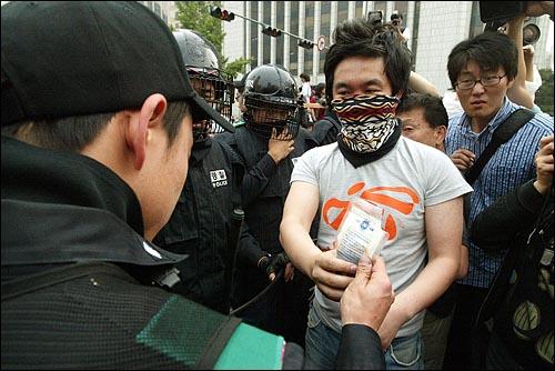 미국산쇠고기 수입 전면개방 반대 72시간 릴레이 농성 나흘째인 8일 새벽 서울 세종로네거리에서 밤을 새워 격렬한 시위가 벌어진 가운데 한 시위자가 경찰에게 보약 한 봉지를 건네고 있다.