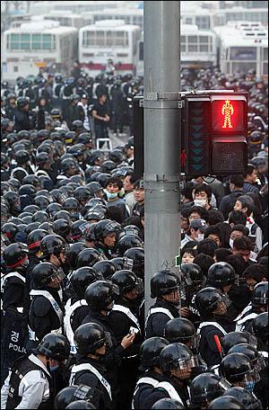 청와대 진입로인 서울 세종로 사거리에서 밤샘 농성을 벌인 시위대를 8일 새벽 경찰이 인도로 밀어내며 강제해산시키고 있다. 시위대가 끌어낸 전경차 자리 뒤로도 수십대의 차량이 배치돼있다.