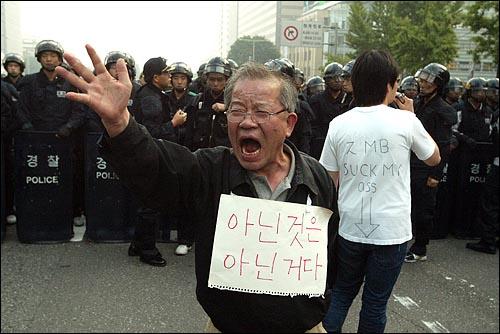 미국산쇠고기 수입 전면개방 반대 72시간 릴레이 농성 나흘째인 8일 새벽 서울 세종로네거리에서 밤을 새워 격렬한 시위가 벌어진 가운데 경찰이 시민들을 강제해산시키기 위해 작전에 나서자 한 할아버지가 경찰앞에 나서 이명박 정부를 규탄하고 있다.
