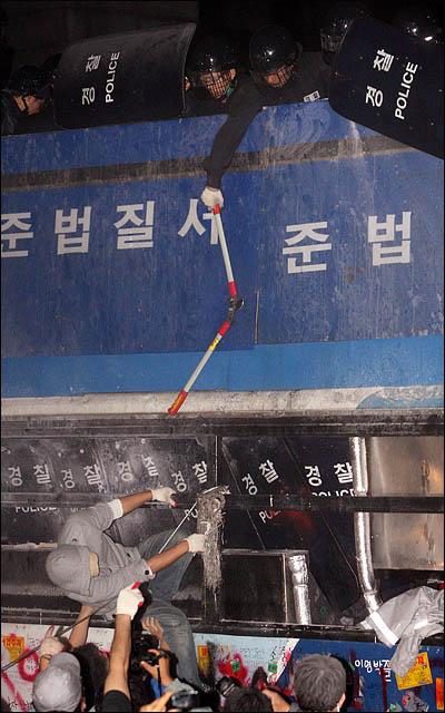 8일 새벽 서울 세종로 사거리에서 청와대 방향으로의 진입을 막고 있는 전경차를 시위대가 밧줄로 묶어 끌어내려하자 경찰이 절단기를 내려치고 있다.
