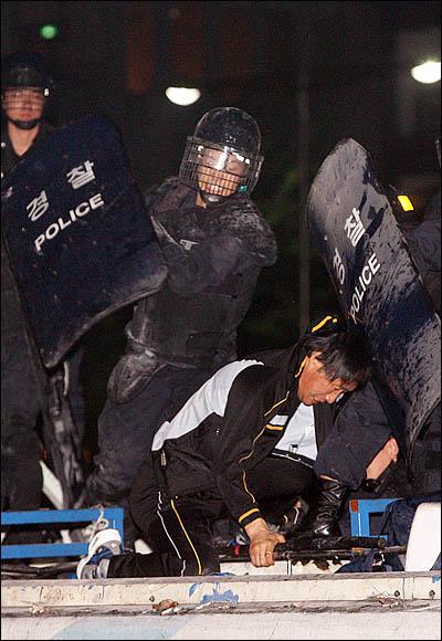 8일 새벽 서울 세종로 사거리에서 청와대 방향으로의 진입을 막고 있는 전경차의 지붕에 올라탄 시위자를 경찰이 방패로 가격하고 있다.