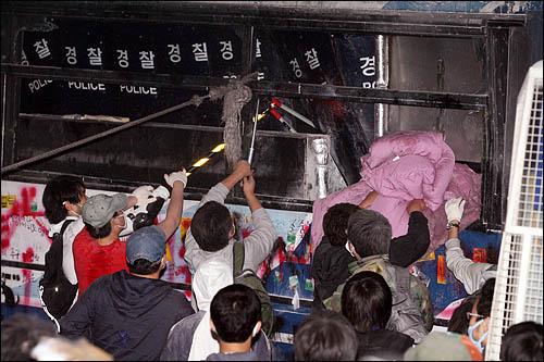 8일 새벽 서울 세종로 사거리에서 청와대 방향으로의 진입을 막고 있는 전경차를 시위대가 밧줄로 묶어 끌어내려하자 경찰이 절단기로 밧줄을 끊고 있다.