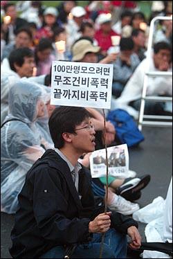 미국산 쇠고기 수입 전면개방 반대 72시간 릴레이 농성이 마무리 된 가운데 8일 저녁 서울시청앞 광장에서 32차 촛불문화제가 열리고 있다. 한 시민이 10일 예정된 100만 촛불대행진을 성사시키기 위해 '비폭력'을 해야한다고 주장하는 종이깃발을 들고 있다.