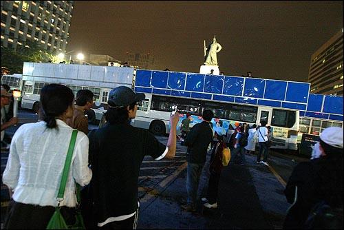 미국산 쇠고기 수입 전면개방 반대 72시간 릴레이 농성이 마무리 된 가운데 8일 저녁 서울시청앞 광장에서 열린 32차 촛불문화제에 참석했던 시민들이 세종로네거리를 가로막은 경찰들을 휴대폰으로 촬영하고 있다.
