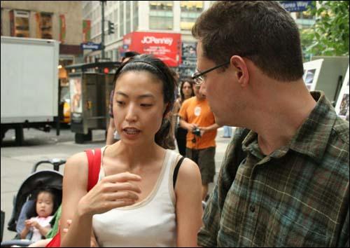 뉴욕 촛불 모임 한인 2세인 김선 씨는 지나가는 미국인들 붙잡고 촛불 모임의 취지와 경위에 대해서 설명했다.`