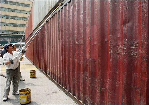 10일 오후 경찰이 광화문 사거리 북쪽 입구에 콘테이너를 2층으로 쌓아놓은 가운데, 인부들이 콘테이너에 그리스를 두껍게 칠하고 있다.