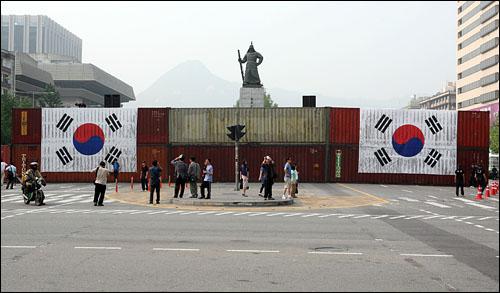 10일 오후 서울 세종로 사거리 북쪽길에 콘테이너 장벽이 설치된 가운데 대형 태극기 2개가 콘테이너 벽에 걸려있다.