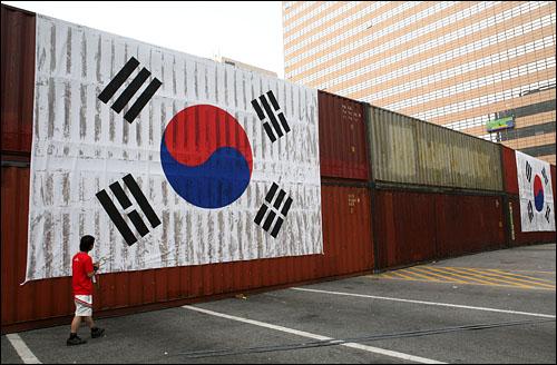 10일 오후 서울 세종로 사거리 북쪽길에 콘테이너 장벽이 설치됐다. 그리스를 두껍게 바른 위에 태극기를 걸쳐 놔 태극기가 더럽혀져 있다.