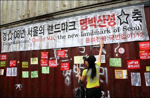 10일 오후 경찰이 설치한 '콘테이너 장벽'에 촛불집회 참가자들이 '경축 08년 서울의 랜드마크 명박산성' 이라고 적힌 현수막과 집회 구호가 적힌 피켓을 붙였다. 그 앞에서 기념촬영을 하고 있는 한 시민.