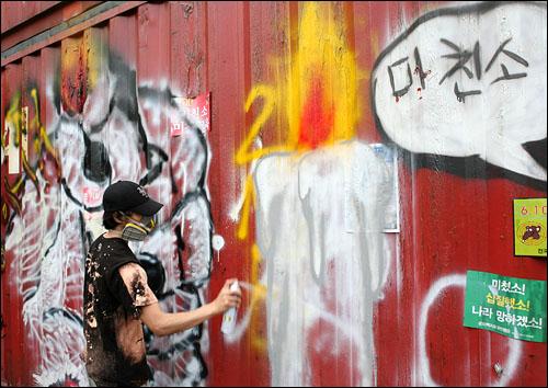 10일 오후 경찰이 설치한 '콘테이너 장벽'에 한 시민이 촛불 그라피티(벽그림)를 그리고 있다