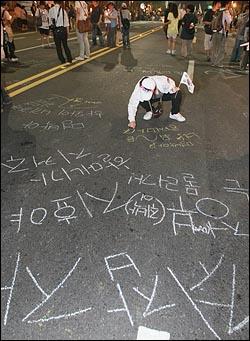 미국산 쇠고기 수입 전면 개방을 반대하는 학생과 시민들이 10일 밤 서울 세종로 동화면세점 앞에서 열린 대규모 '미국산 쇠고기 수입 반대' 촛불문화제를 마친뒤 종각으로 거리행진을 하며 한 시민이 차도에 이명박 대통령의 대한 낙서를 하고 있다.